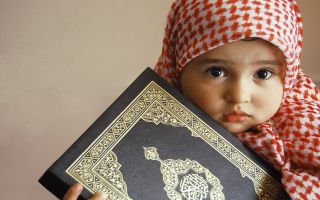 Cute little muslim baby holing Holy Quran1